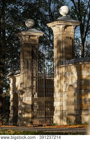 The Ancient Ornate Neoclassical Entrance Gate Of Tyshkevich Manor In The Park Alley Is Lit By The Ev