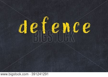 Chalk Handwritten Inscription Defence On Black Desk