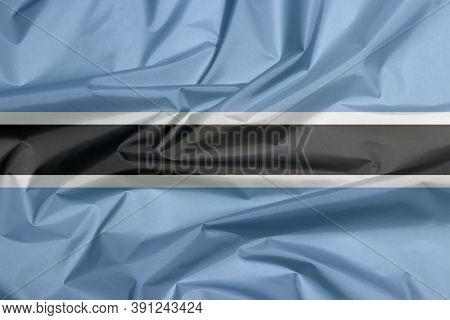 Fabric Flag Of Botswana. Crease Of Botswana Flag Background, Black Stripe With A Thin White Frame On