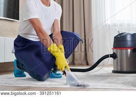 Man Cleaning Carpet In The Living Room Using Vacuum Cleaner At Home. Cleaning Service Concept
