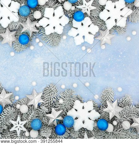 Christmas decorative border with snowflakes, stars & ball decorations with snow covered fir on pastel blue background. Xmas & New year festive design. Flat lay, top view.