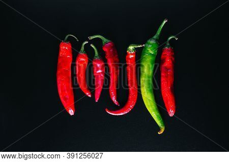 Fresh Chili Peppers Of Red And Green Color Evenly Arranged On A Black Background.