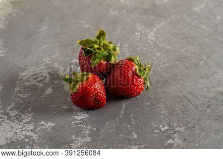 Three Fresh Juicy Strawberries Lie On A Concrete Background.