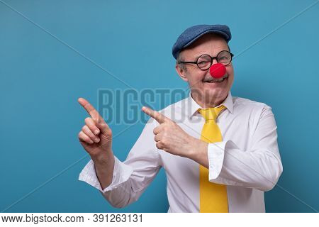 Senior Cheerful Man With Red Nose Pointing With Index Finger Aside.