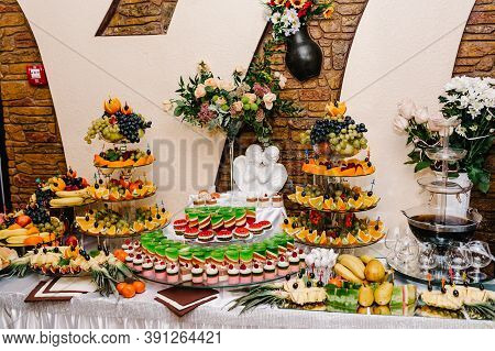 Sweet Table Decorated In Restaurant. Dessert Table For A Party Goodies With Sweets, Cakes, Candy, Bu