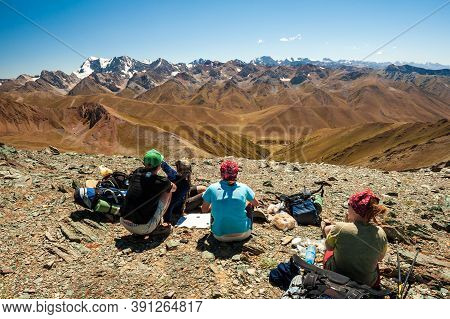 Group Of Trekkers Resting In Rocky Pass With Mountain Top Wiews In High Mountains. Young Men And Wom