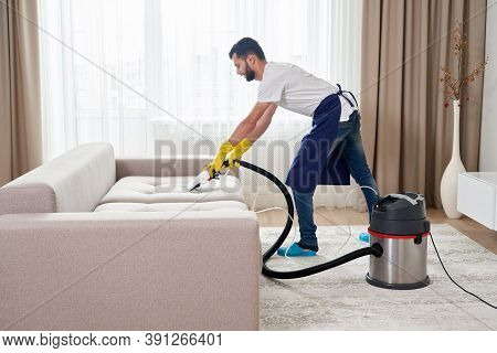 Close-up Of Housekeeper Holding Modern Washing Vacuum Cleaner And Cleaning Dirty Sofa With Professio