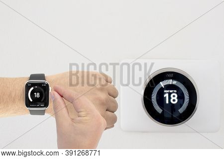 Calgary, Alberta, Canada. Oct 23, 2020. A Person Controlling A Nest Smart Thermostat From An Apple W