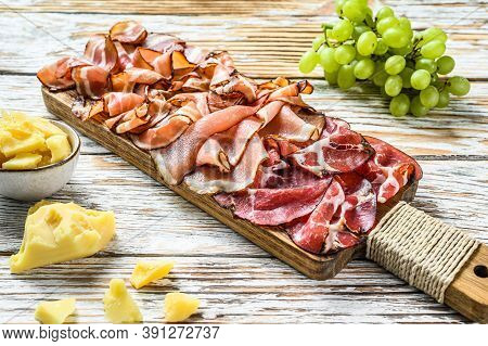 Set Of Cold Cured Italian Meat Ham, Prosciutto, Pancetta, Bacon. White Wooden Background. Top View