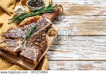 Grilled Porterhouse Steak On A Chopping Board. Cooked Beef Meat. White Wooden Background. Top View.