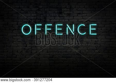 Neon Sign On Brick Wall At Night. Inscription Offence