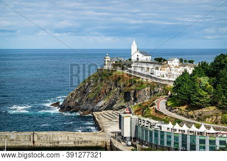 Luarca, Asturias, Spain - October 10, 2020: Picturesque Chapel With Cementery And A Lighthouse Overl