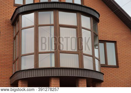 One Large Closed Glazed Balcony On The Brown Wall Of A Private House With Windows