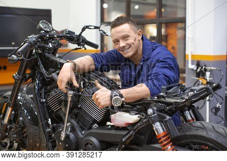 Smiling Repairman In A Repair Shop Near A Motorcycle Shows Thumbs Up.