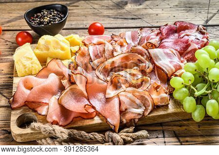 Set Of Cold Cured Italian Meat Ham, Prosciutto, Pancetta, Bacon With Parmesan And Grape. Wooden Back
