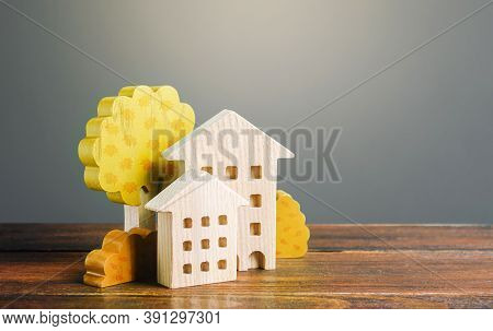Wooden Figurines Of Residential Buildings And Autumn Yellow Trees. Buying Or Renting A House. Sale O
