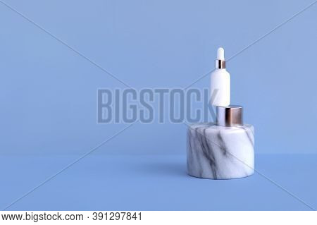 Natural Organic Cosmetic Serum In A White Glass Bottle With A Dropper Pipette On A Marble Aluminum P