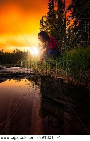 Girl Crouched By A Scenic Lake Reflecting On Life In Canadian Nature. Dramatic Colorful Sunset Artis