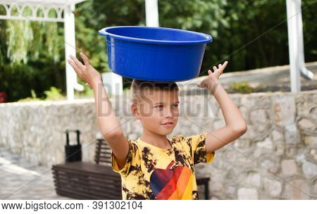 Boy Child With A Basin On His Head. The Child Put A Basin On His Head. Funny Goofy Boy Outdoor