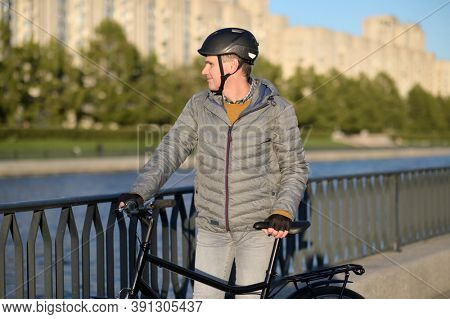 Mature Caucasian man in casual clothing and bike helmet standing with his bicycle on a canal embankment in a city and looking away