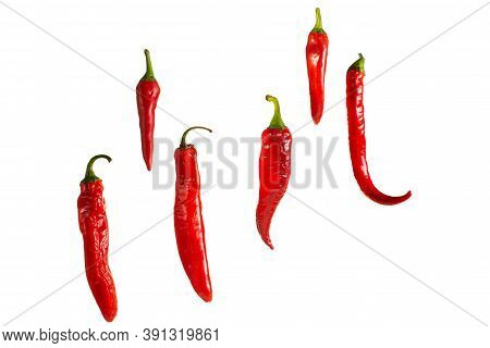 Fresh Red Chili Peppers Hanging In The Air On A White Background. Isolate For Copying.