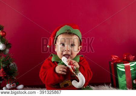 Sweet One-year-old Boy Dressed As An Elf Sitting, Holding A Typical Christmas Stick In His Mouth