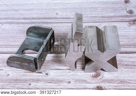 Sheet Metal Bending Tool And Equipment On A Wooden Background. Bend Tools, Press Brake Punch And Die