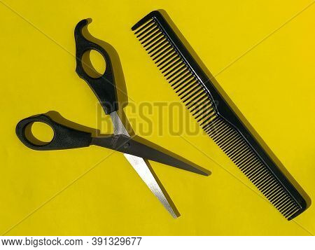 Hairdressing Scissors And Comb On A Bright Yellow Background. Hairdresser Tools. Hairdressing Salon