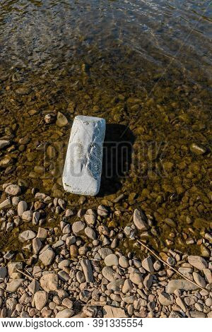 Closeup Of Large Piece Of Styrofoam In Shallow Water Beside Riverbank.