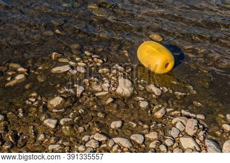 Closeup Of Large Yellow Styrofoam Buoy In Shallow Water Beside Riverbank.