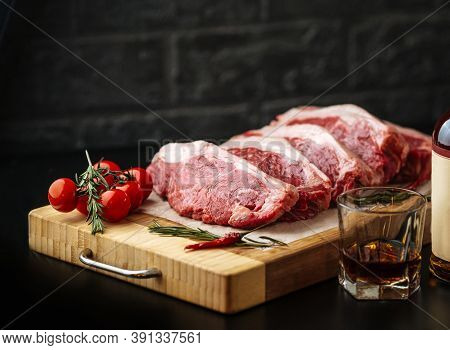 Raw Uncooked Steak Striploin New York On A Wooden Board With Tomatoes And Rosemary
