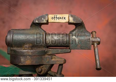 Concept Of Dealing With Problem. Vice Grip Tool Squeezing A Plank With The Word Offence