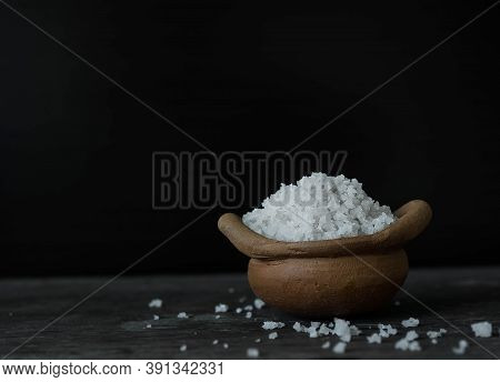 Large White Sea Salt In Clay Pot On Wood With Black Background.  Contains Iodine.  For Eat Healthy O