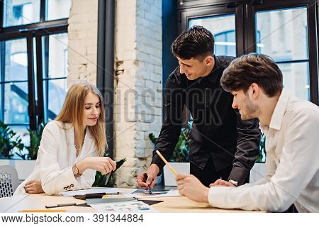 Businessman Showing Business Graph To Colleagues At Desk In Office