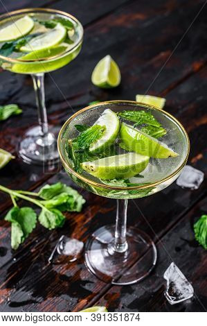 Fresh Drink Lemonade Mojito. Mojitos With Mint Leaves, Lime And Ice. Black Wooden Background. Top Vi