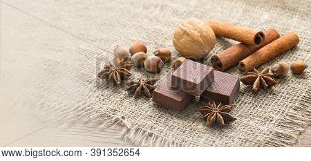 Pieces Of Chocolate, Cinnamon Sticks, Walnuts And Star Anise Stars. Confectionery Shop Advertising A