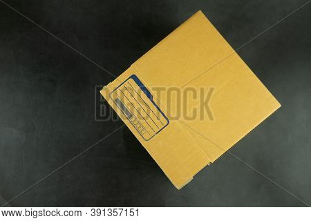 Close Up Of Small Packet Of Brown Box With Empty For Write Address Sender On A Black Background