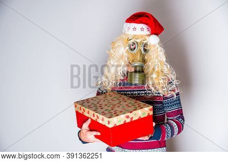 Trans Person In Face Protection Mask With Blond Curly Hair With Gift In Hand In Christmas