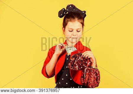 Born To Be Rich. Little Girl Put Dollars In Money Bag. Small Child Save Cash Money. Money Savings. D