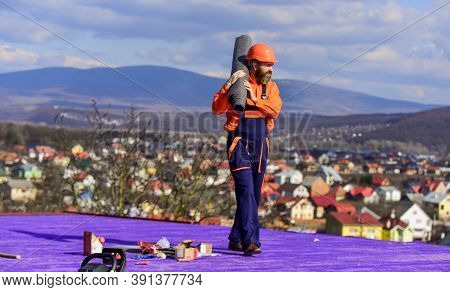 Roof Industrial. Roofer Contractor Laying Rooftop With Protective Helmet. Man Inspecting Damaged Roo