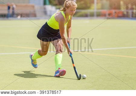 Younf Female Hockey Player Leading The Ball