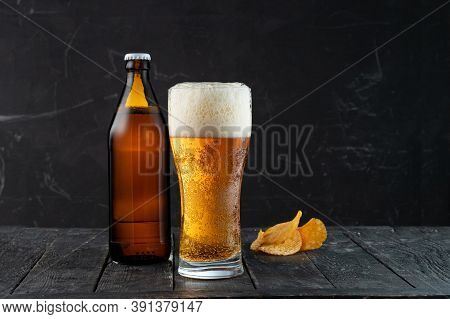 Freshly Poured Beer And Potato Chips. Beer And Snack. The Bright Light Of The Beer. High Beer Foam.