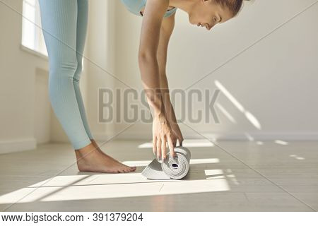Calm Young Woman Unrolling Yoga Mat Before Practicing Asanas And Meditating In Gym