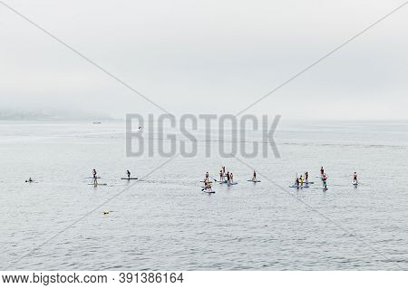 Sanxenxo, Spain - August 26, 2020: A Group Of Young People Enjoy Practising Paddle Surf In The Ria D