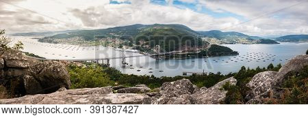 Panorama View Of The Ria De Vigo Estuary From Redondela On A Cloudy Summer Afternoon, With The Recen