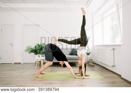 Beautiful Sporty Fit Couple, Young Man And Woman, Practicing Yoga Together At Home, Doing Paired Gym