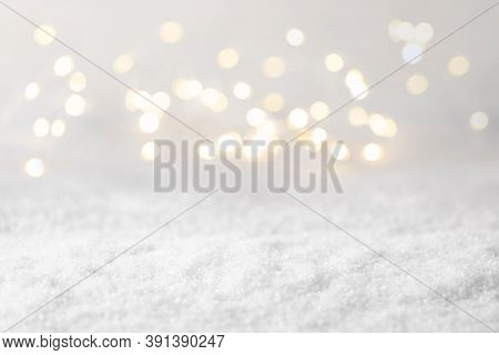 Blurred Christmas Lights And Snow. Bokeh Winter Background. Defocused