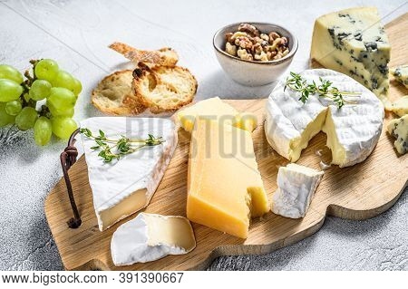 Cheese Board With French Camembert, Brie, Parmesan And Blue Cheese, Grapes And Walnuts. White Backgr