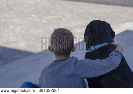 View From The Back Of The Child Sitting In One With Black Labrador In Blue Collar Outside. An Eight-