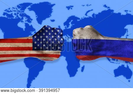 Governments Conflict Concept. Male Fists Colored In Usa And Russian Flags On World Map Background. C